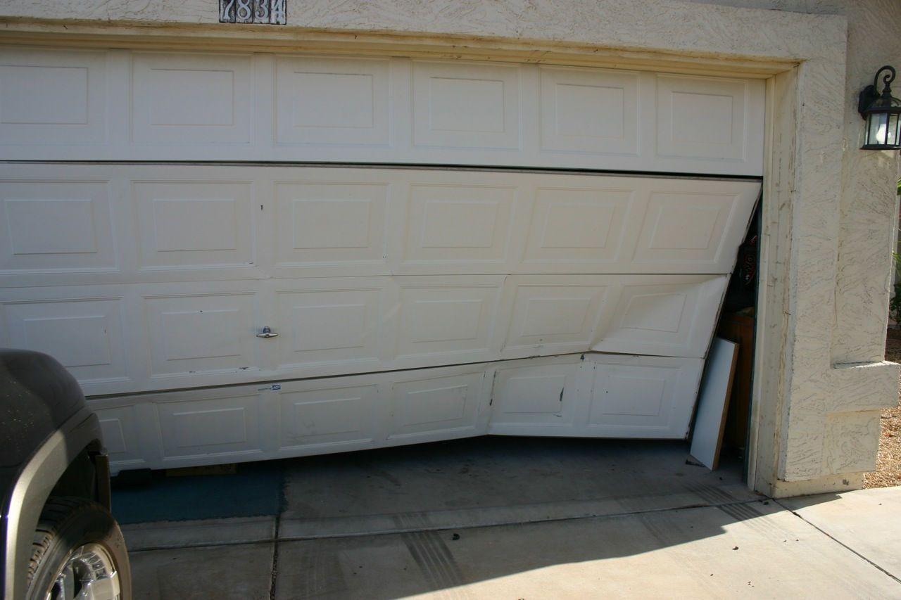 Damaged and wrecked garage door in need of an emergency fix